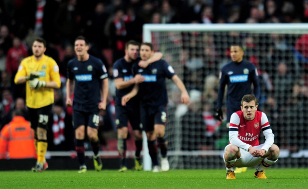 Jack Wilshere looks on in despair as Blackburn players celebrate their FA Cup victory.