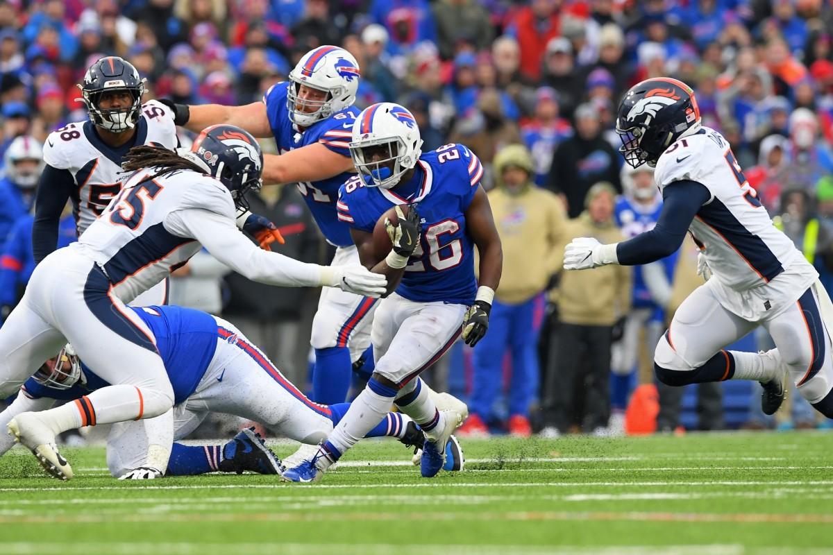 Buffalo Bills running back Devin Singletary (26) runs with the ball between the defense of Denver Broncos linebacker A.J. Johnson (45) and inside linebacker Todd Davis (51) during the third quarter at New Era Field.