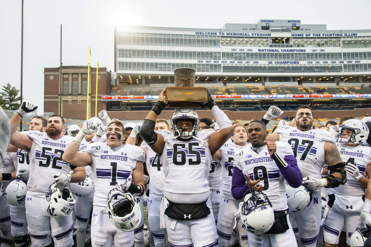 The Northwestern Wildcats celebrate with the Land of Lincoln Trophy after defeating the Illinois Fighting Illini at Memorial Stadium.