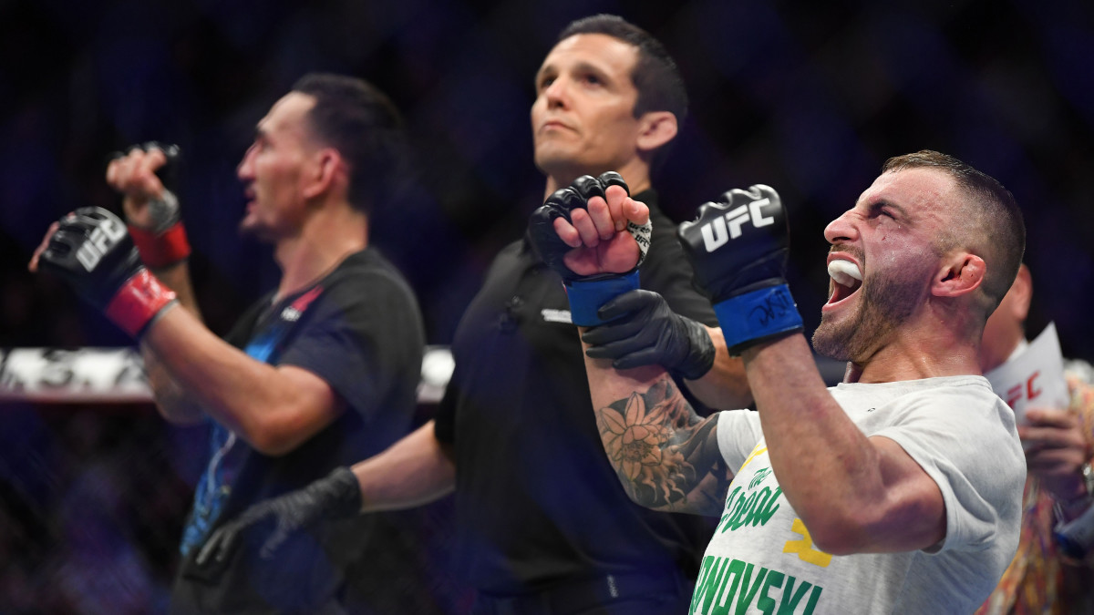 Dec 14, 2019; Las Vegas, NV, USA; Alexander Volkanovski (blue gloves) reacts after defeating Max Holloway (red gloves) during UFC 245 at T-Mobile Arena