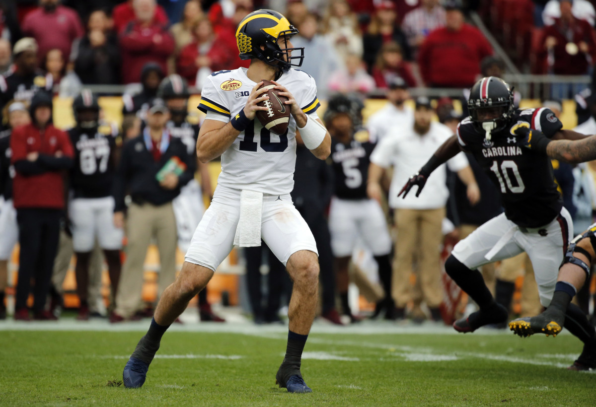 Michigan quarterback Brandon Peters (18) drops back against the South Carolina Gamecocks during the first quarter of the 2018 Outback Bowl at Raymond James Stadium.
