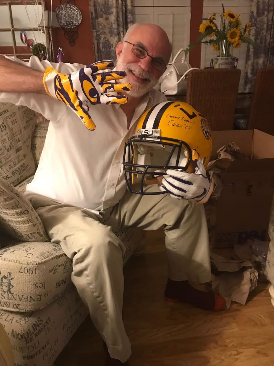Jeff Berteau, the father of Ed Aschoff's fiancée Katy, is seen here posing for a photo with a helmet and gloves that the LSU equipment staff sent to him earlier this season.