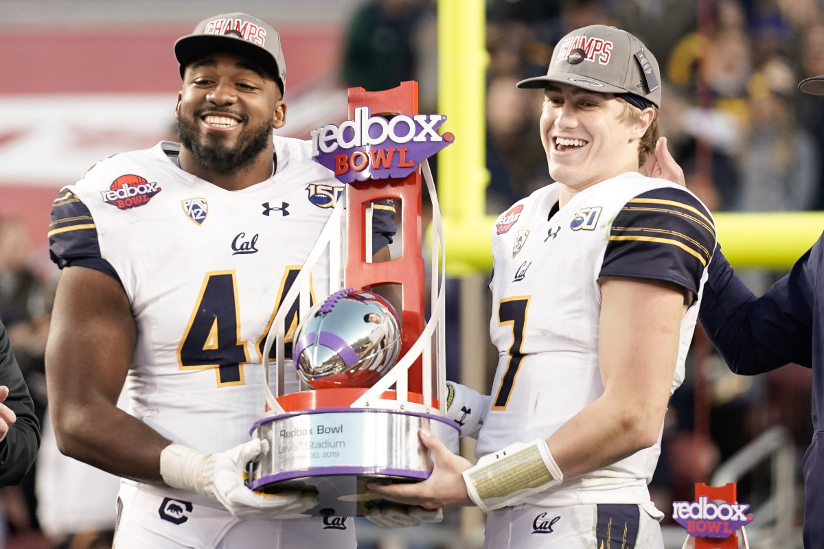 California Golden Bears defensive end Zeandae Johnson (44) and quarterback Chase Garbers (7) hold the RedBox trophy after defeating the Illinois Fighting Illini at Levi's Stadium