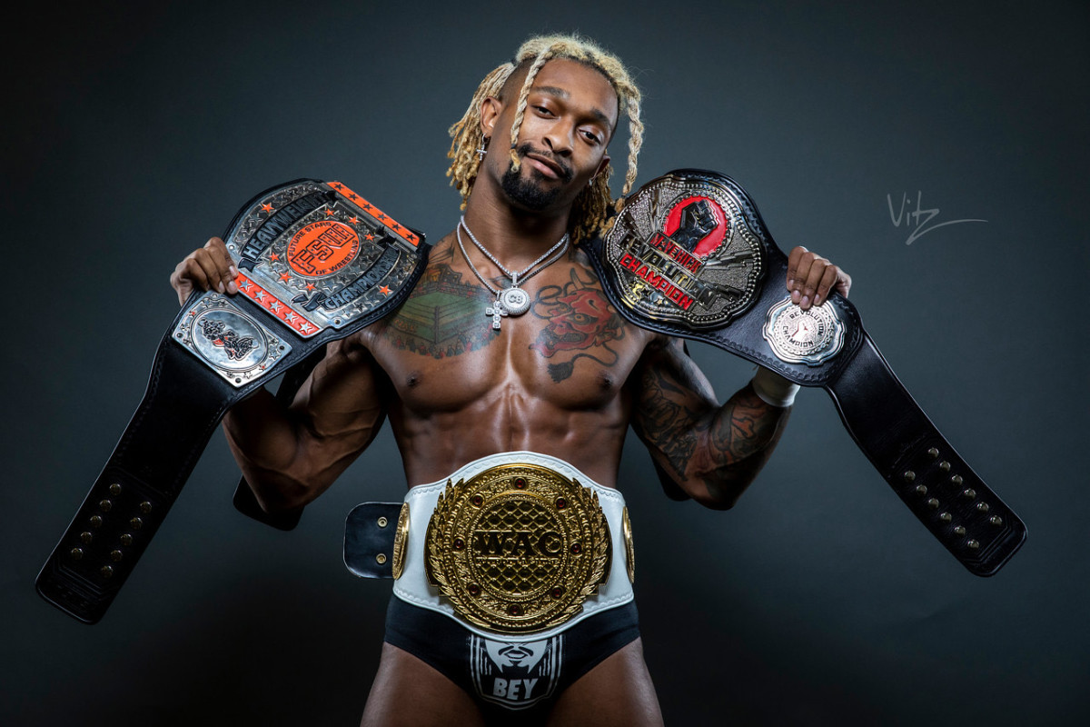 Wrestler Chris Bey with his championship belts