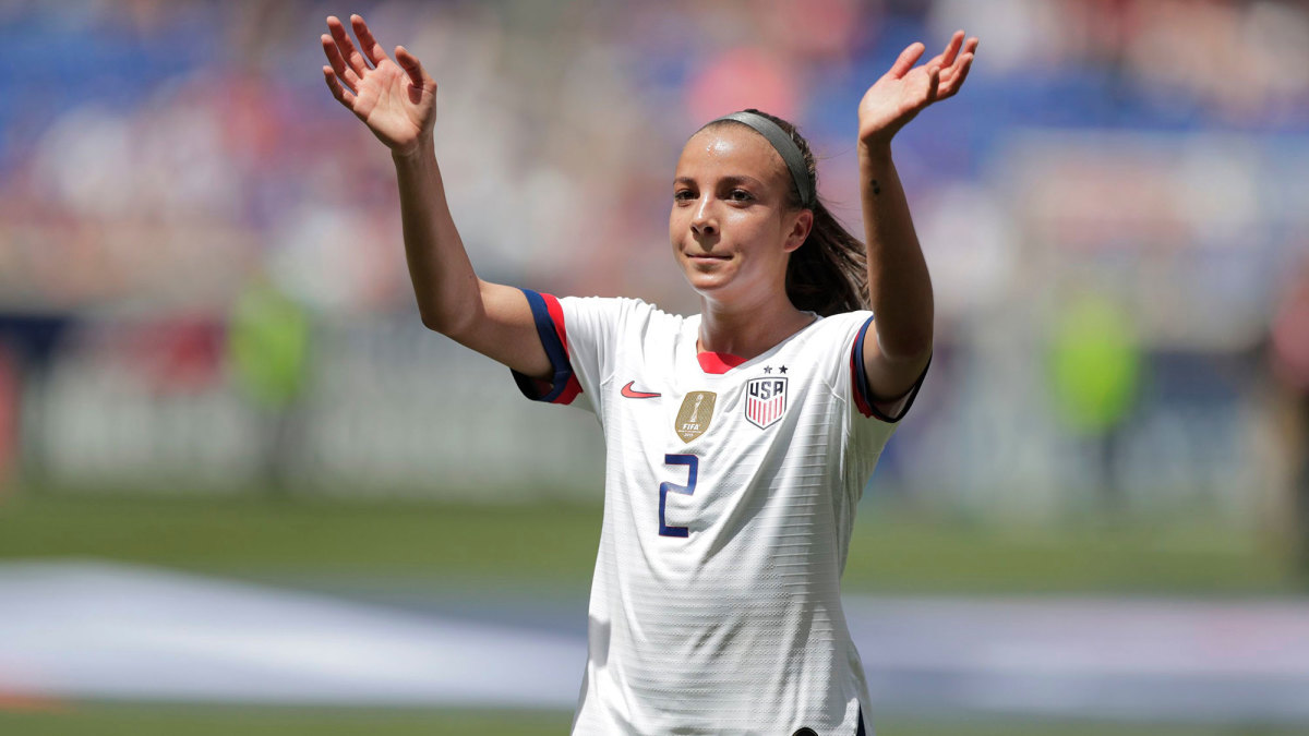 Mal Pugh in a white USWNT jersey with her hands raised