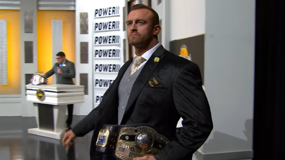 NWA champion Nick Aldis makes his entrance carrying the title belt
