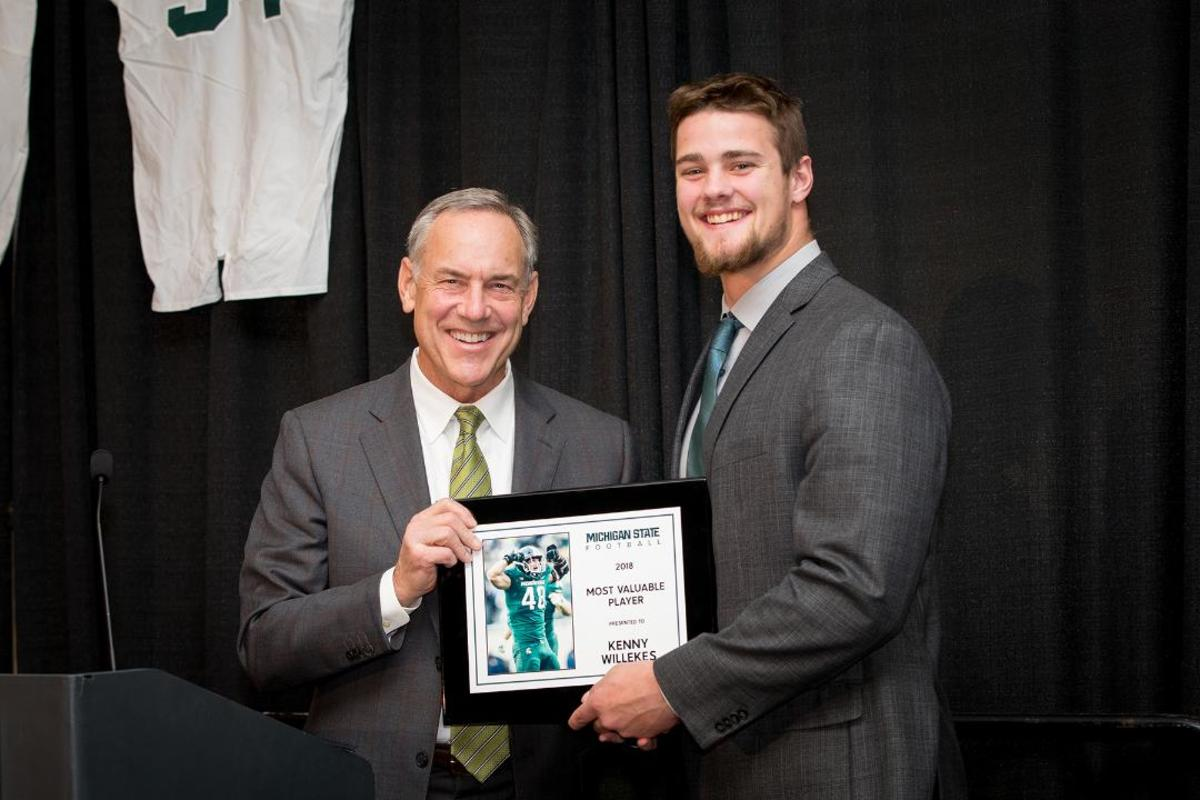 MSU head coach Mark Dantonio presents Kenny Willekes with the Most Valuable Player award at Michigan State's annual banquet on Sunday, Nov. 25 at the Kellogg Center. (PHOTO: Matthew Mitchell, MSU Athletic Communications)