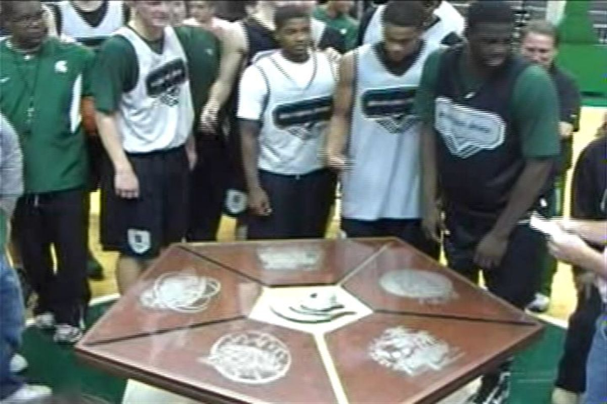 The Izzo Family and Players Circle Around a Hand Made Table for Coach Izzo from Volunteers at the MSU Physical Plant!