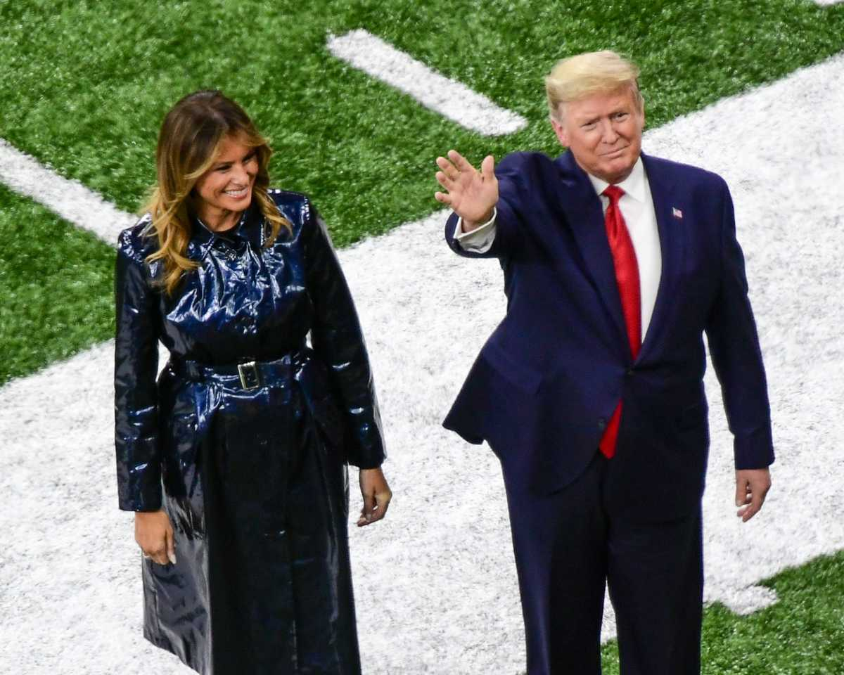 President Donald Trump stands with first lady Melania Trump on the field of the College Football Playoff final