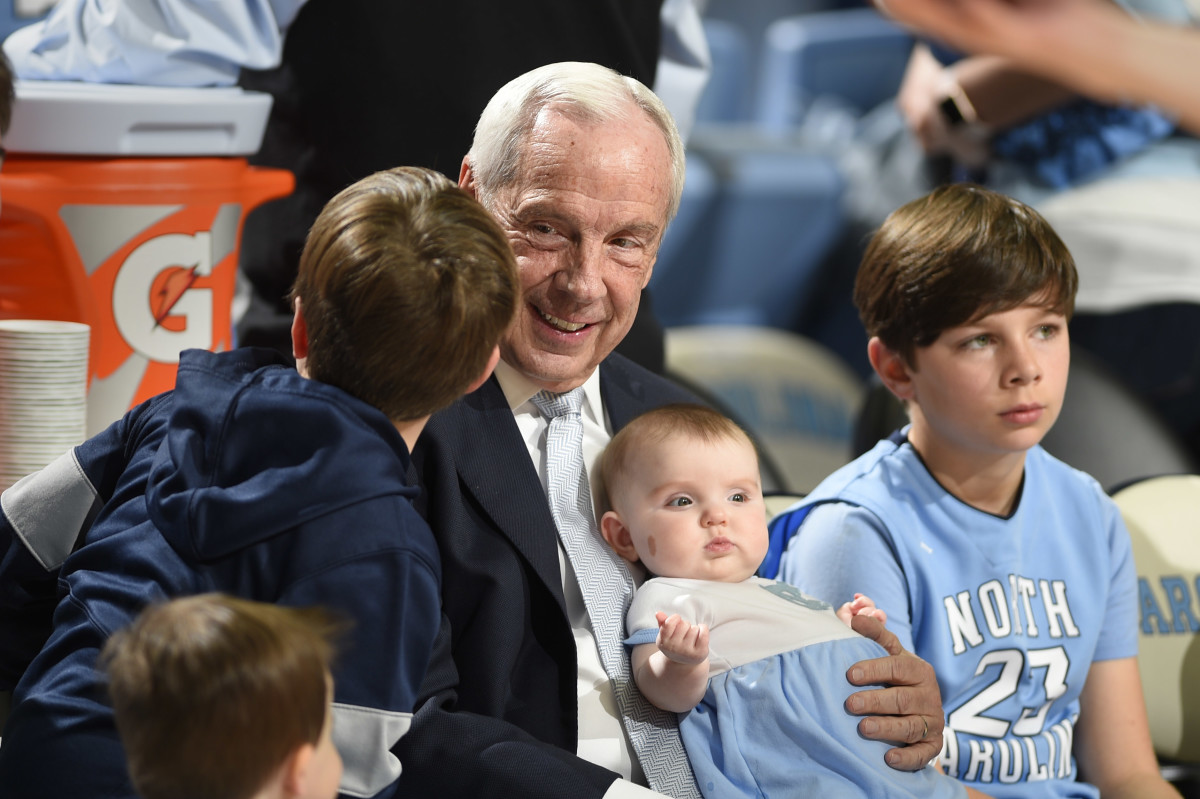 North Carolina Tar Heels head coach Roy Williams holds his granddaughter Kenzie Newlin before a game at Dean E. Smith Center.