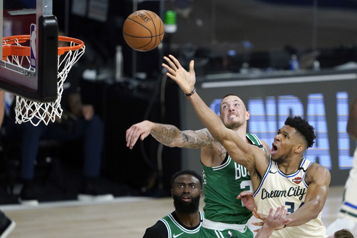 Milwaukee Bucks' Giannis Antetokounmpo, right, heads to the basket as Boston Celtics' Daniel Theis defends during the second half of an NBA basketball game Friday, July 31, 2020,