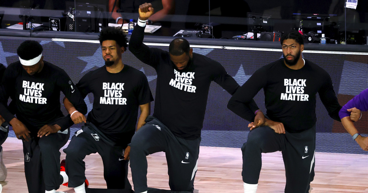 LeBron James and Anthony Davis of the Los Angeles Lakers kneel during the national anthem wearing a Black Lives Matter shirt