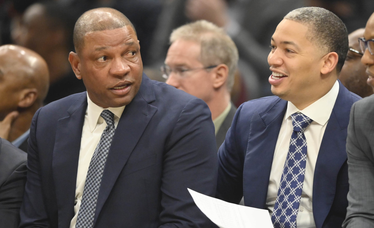 LA Clippers head coach Doc Rivers, left, talks with assistants Tyronn Lue,