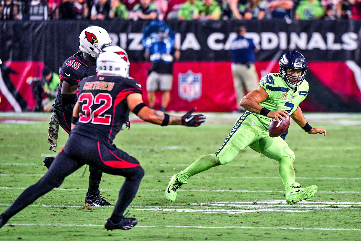 Russell Wilson spins as he tries to evade Cardinals defenders Chandler Jones and Tyrann Mathieu