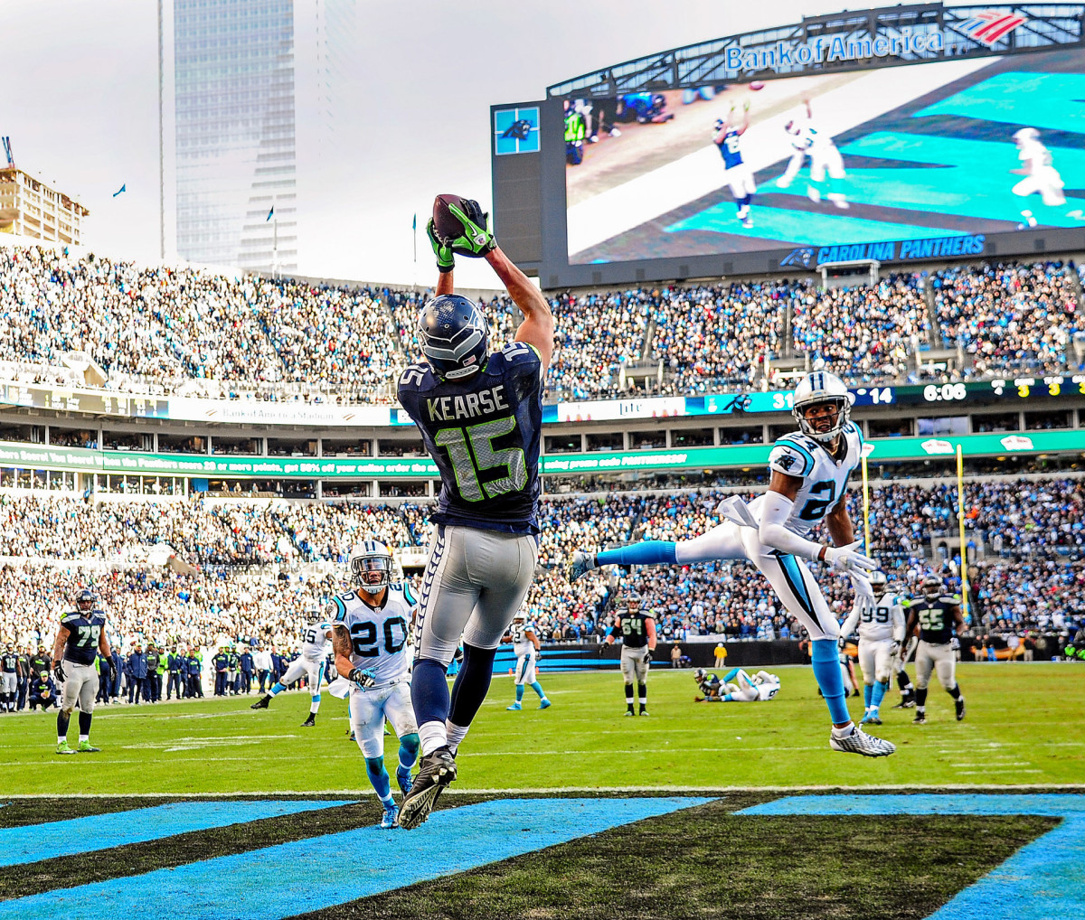Jermaine Kearse catches a touchdown pass from Russell Wilson (on the ground in the background) as Panthers cornerback Josh Norman looks back.