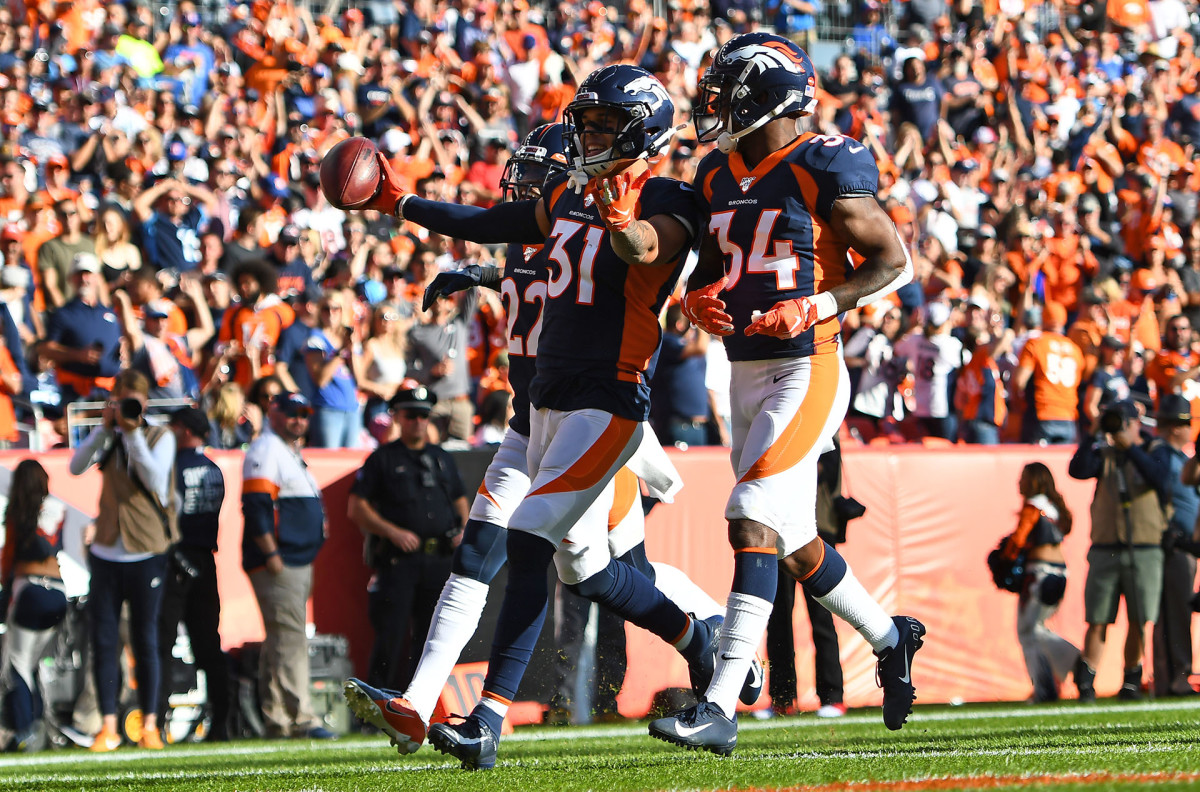 Broncos safety Justin Simmons celebrates an interception with two teammates