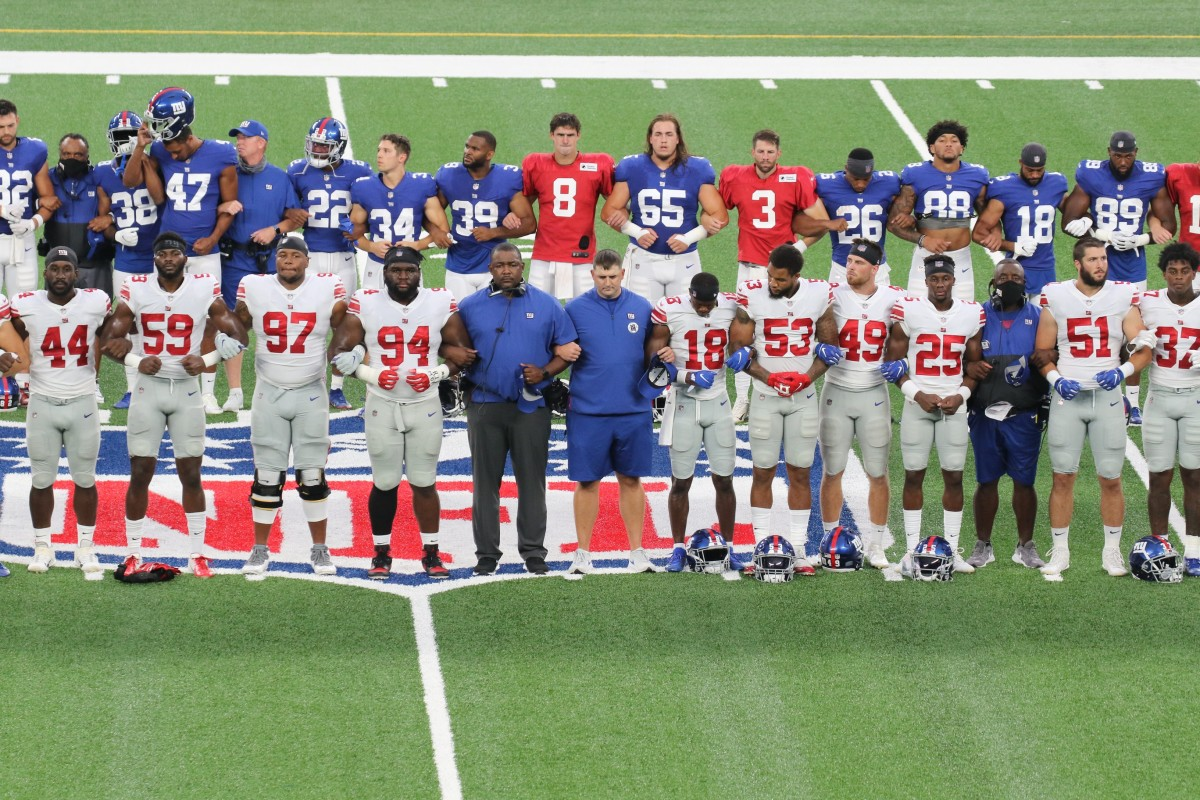 Head coach Joe Judge and his team at midfield linking arms in a call for social justice before the New York Giants play an inter-squad game, the Blue White scrimmage at MetLife Stadium on