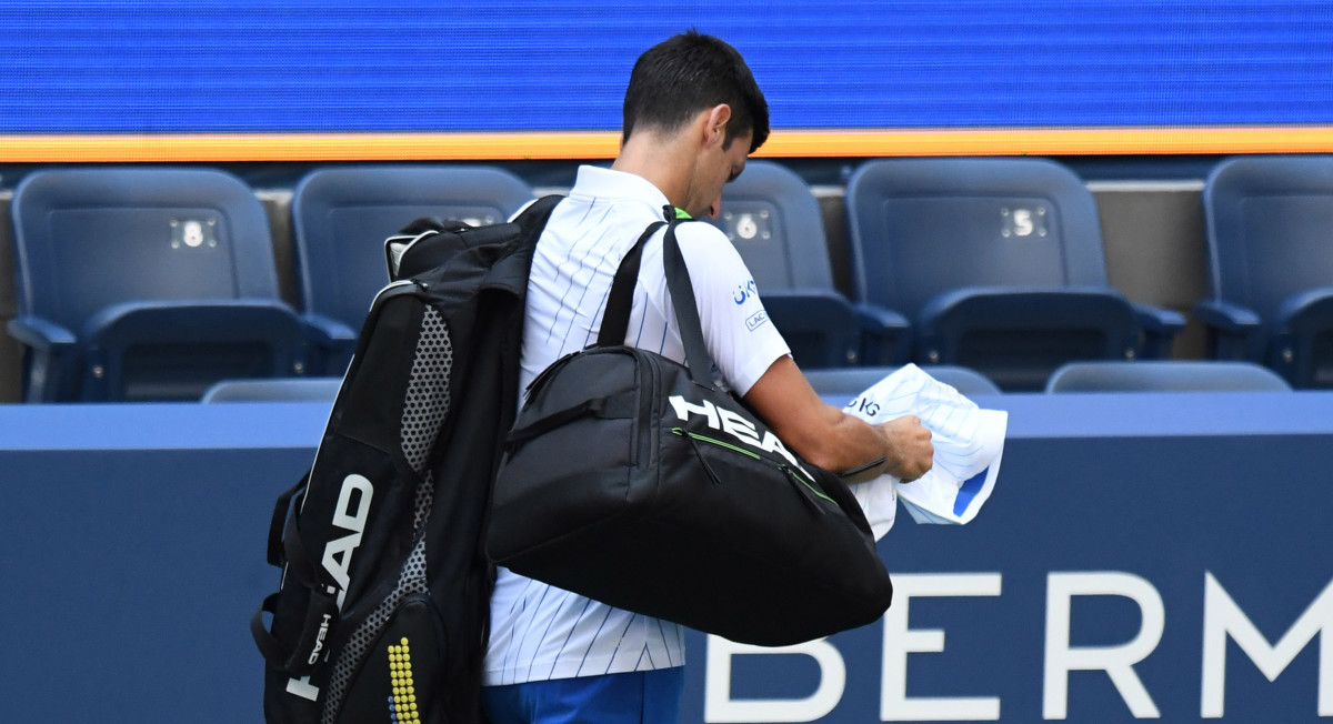 Novak Djokovic of Serbia leaves the court after being defaulted for striking a lines person with a ball against Pablo Carreno Busta of Spain (not pictured) on day seven of the 2020 U.S. Open