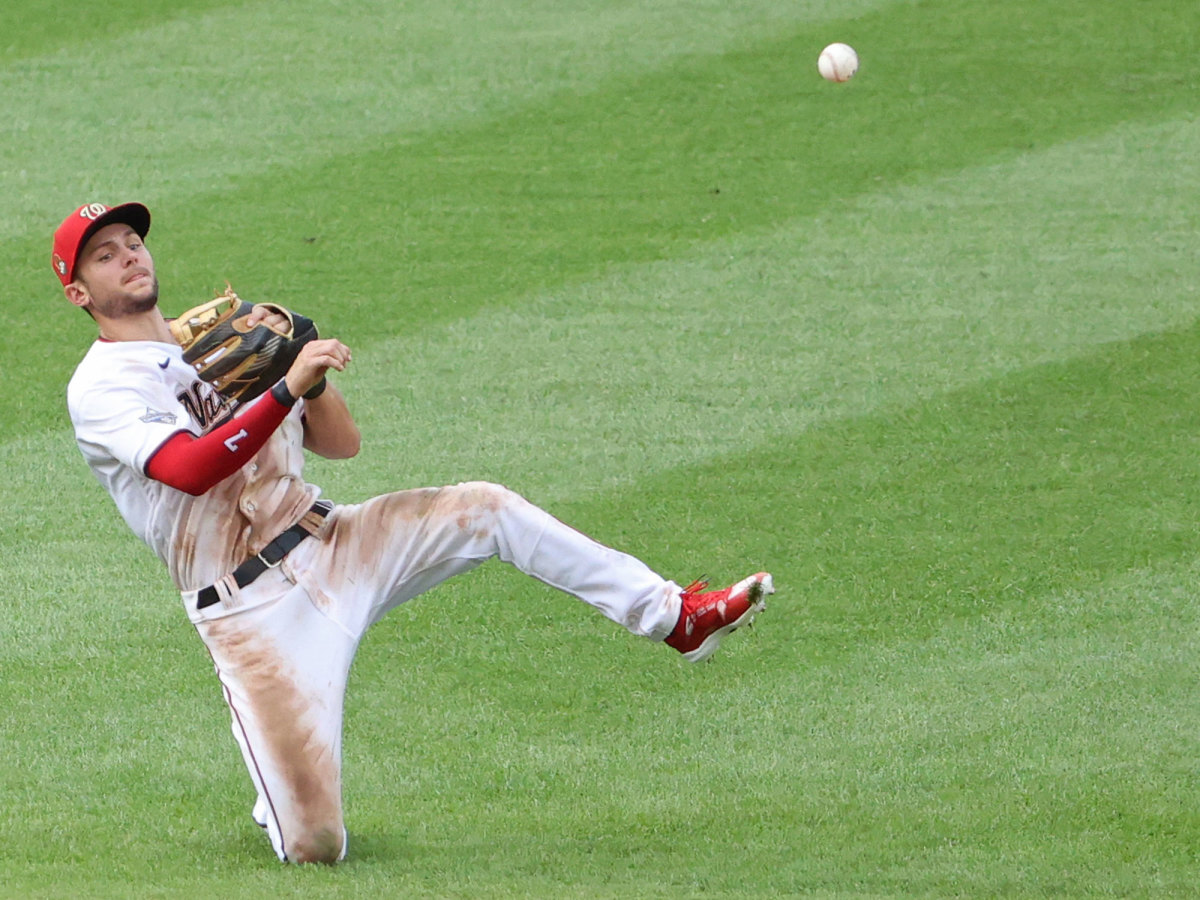 Trea Turner throws from a knee