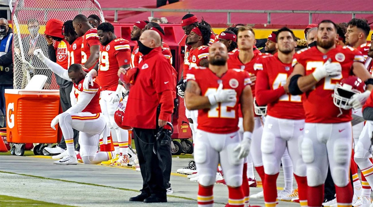 Kansas City Chiefs defensive end Alex Okafor (97) kneels while other teammates stand for the national anthem before their game against the Houston Texans at Arrowhead Stadium.