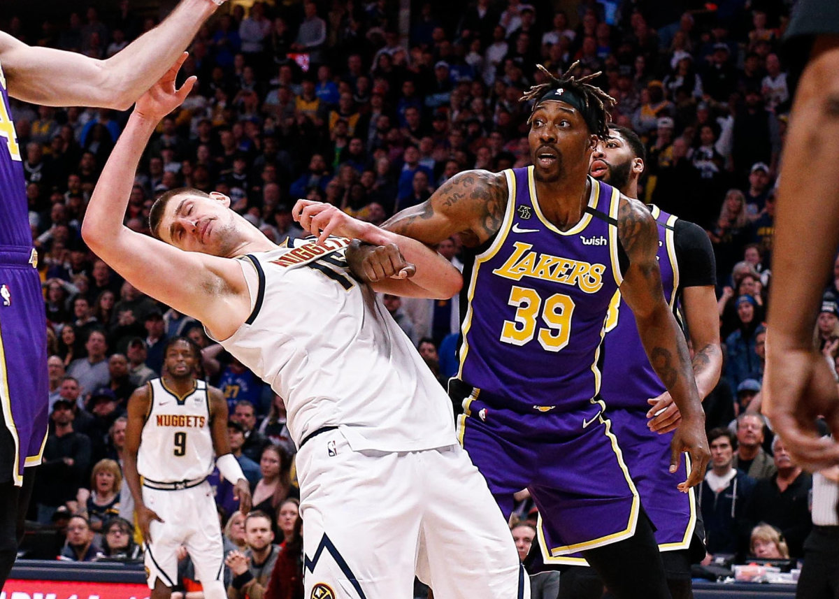 Denver Nuggets center Nikola Jokic (15) battles for a rebound against Los Angeles Lakers guard Alex Caruso (4) and center Dwight Howard (39) in overtime at the Pepsi Center.