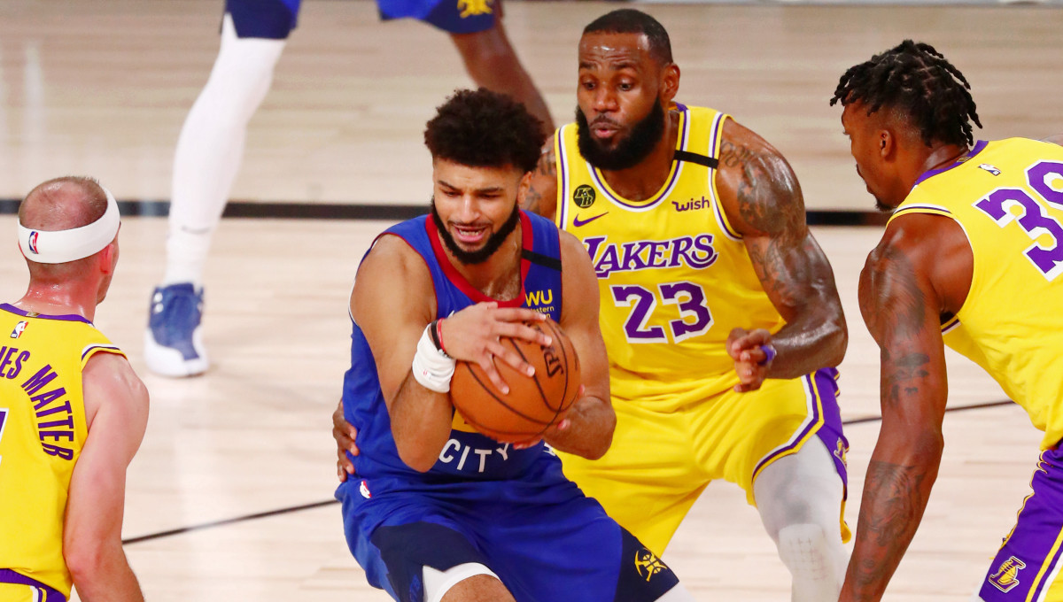 Denver Nuggets guard Jamal Murray (27) holds the ball while defended by Los Angeles Lakers guard Alex Caruso (left) forward LeBron James (center) and center Dwight Howard (right) during the second quarter