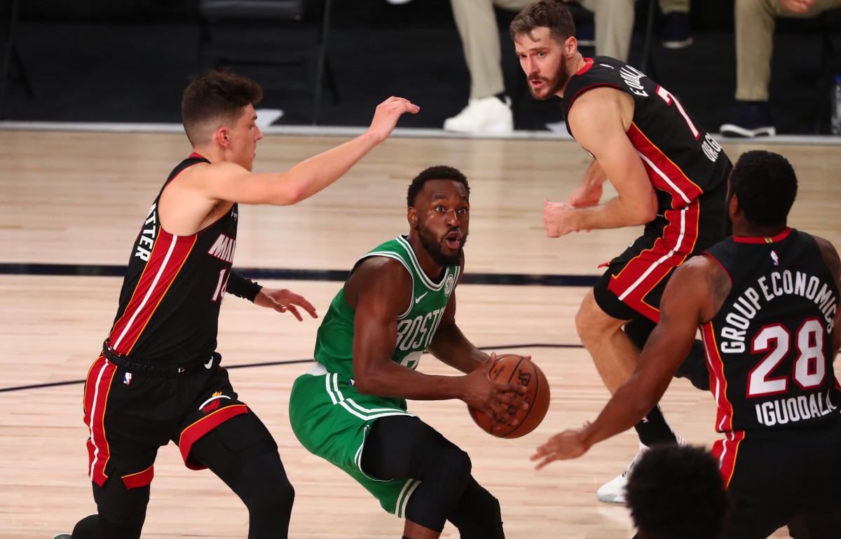 Boston Celtics guard Kemba Walker (middle) drives against Miami Heat guard Tyler Herro (left) and guard Andre Iguodala (28) and guard Goran Dragic (7)