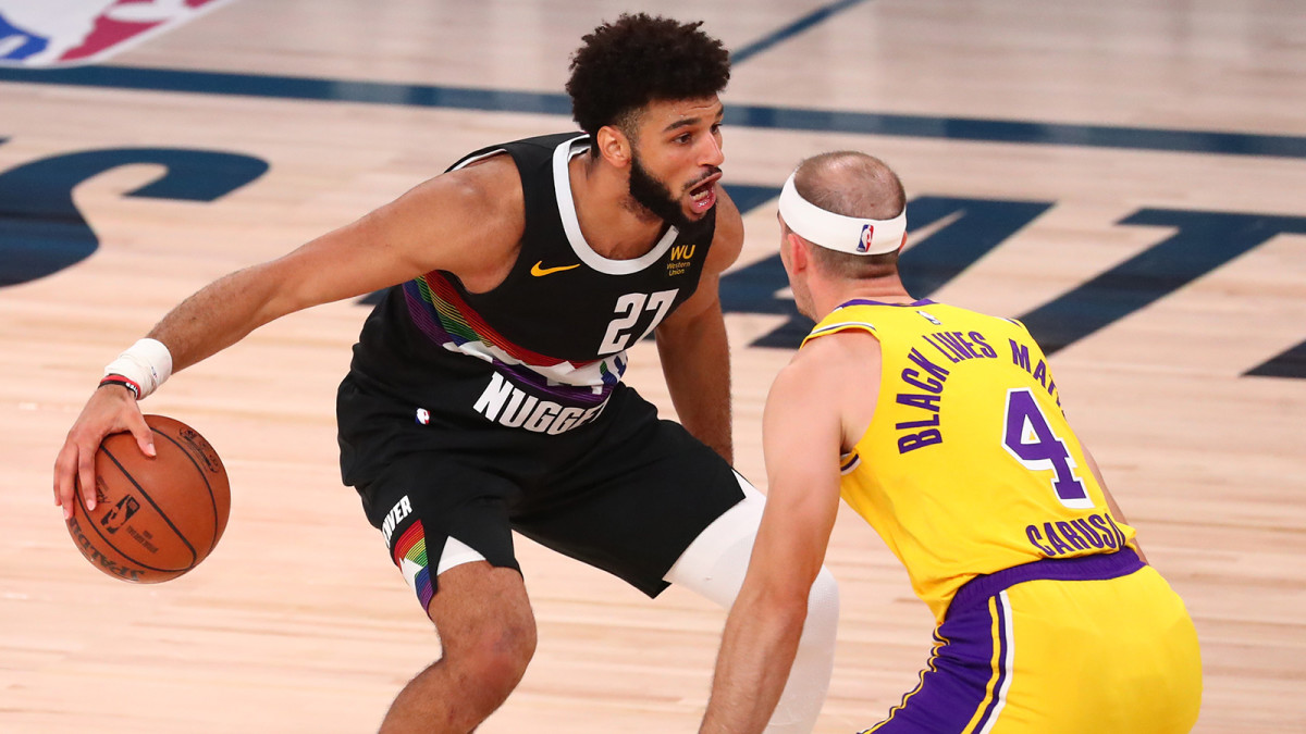 Nuggets guard Jamal Murray dribbles the ball around Los Angeles Lakers guard Alex Caruso