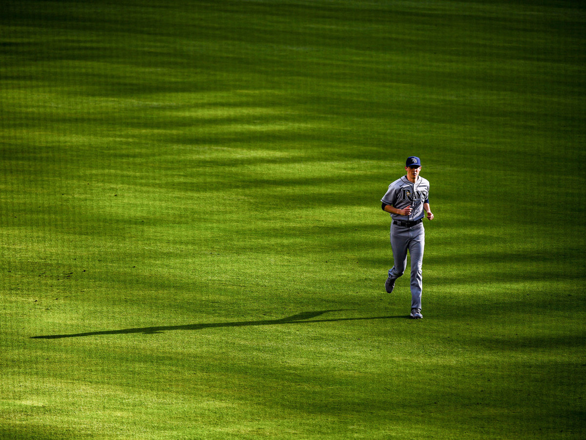 A Rays pitcher runs in the outfield
