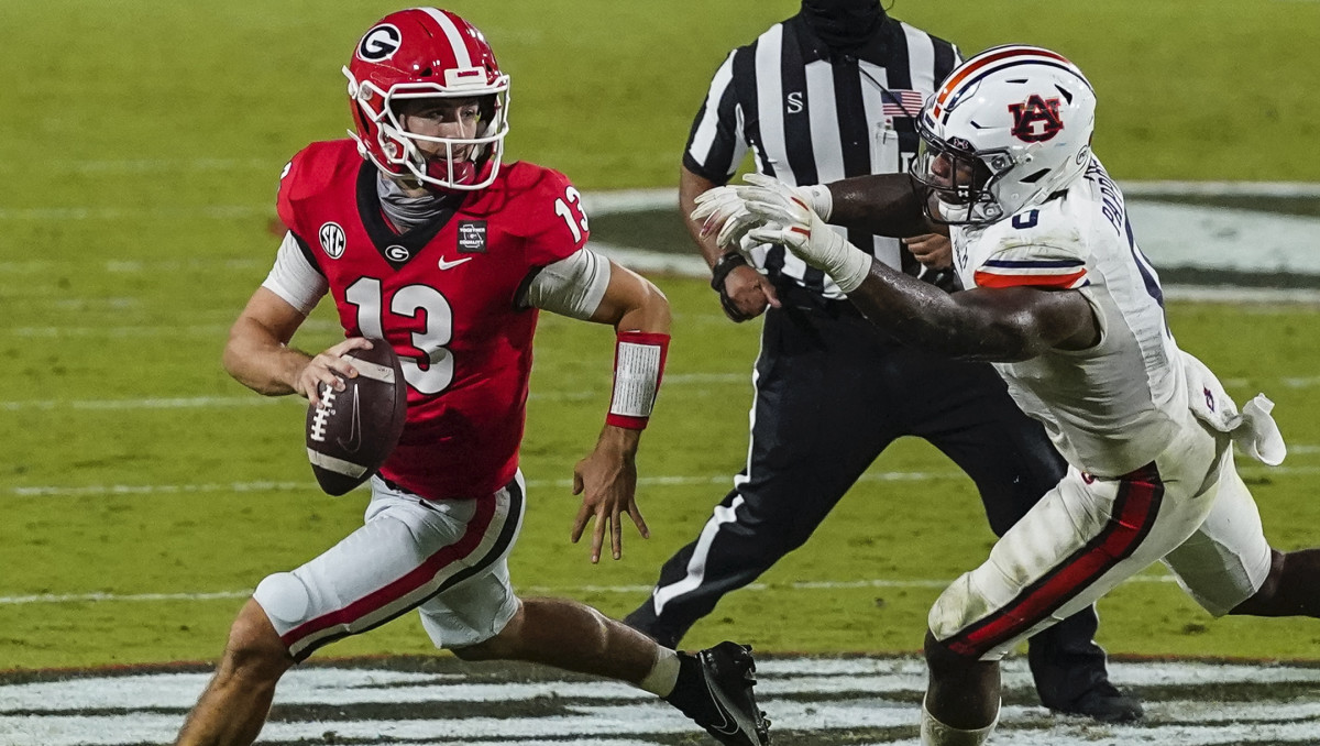 Georgia Bulldogs quarterback Stetson Bennett (13) escapes the pressure of Auburn Tigers Auburn Tigers linebacker Owen Pappoe (0) during the second half at Sanford Stadium.