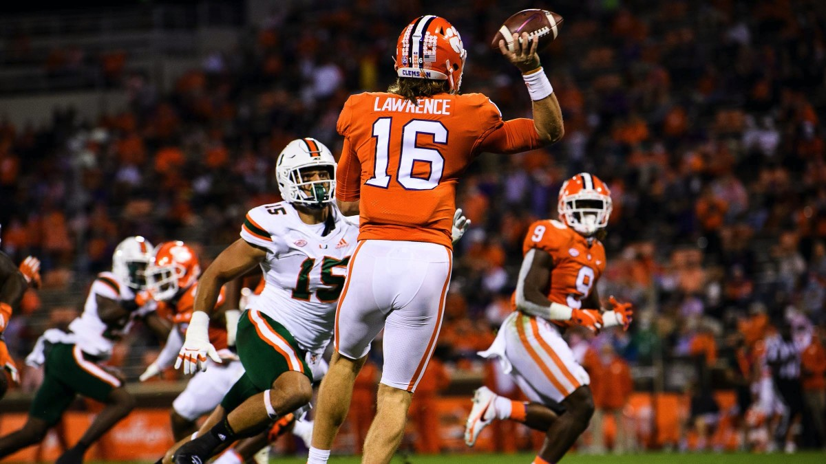 Clemson Tigers quarterback Trevor Lawrence (16) throws to running back Travis Etienne (9) against Miami Hurricanes defensive line Jaelan Phillips (15) during the first quarte at Memorial Stadium.