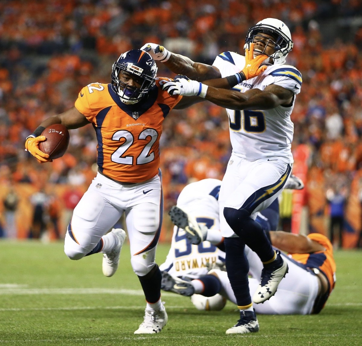 C.J. Anderson fends off a Chargers would-be tackler.