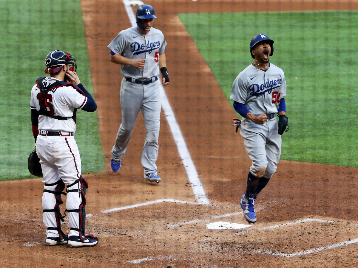 Oct 14, 2020; Arlington, Texas, USA; Los Angeles Dodgers right fielder Mookie Betts (50) celebrates after scoring against Atlanta Braves catcher Travis d'Arnaud (16) during game three of the 2020 NLCS at Globe Life Field.