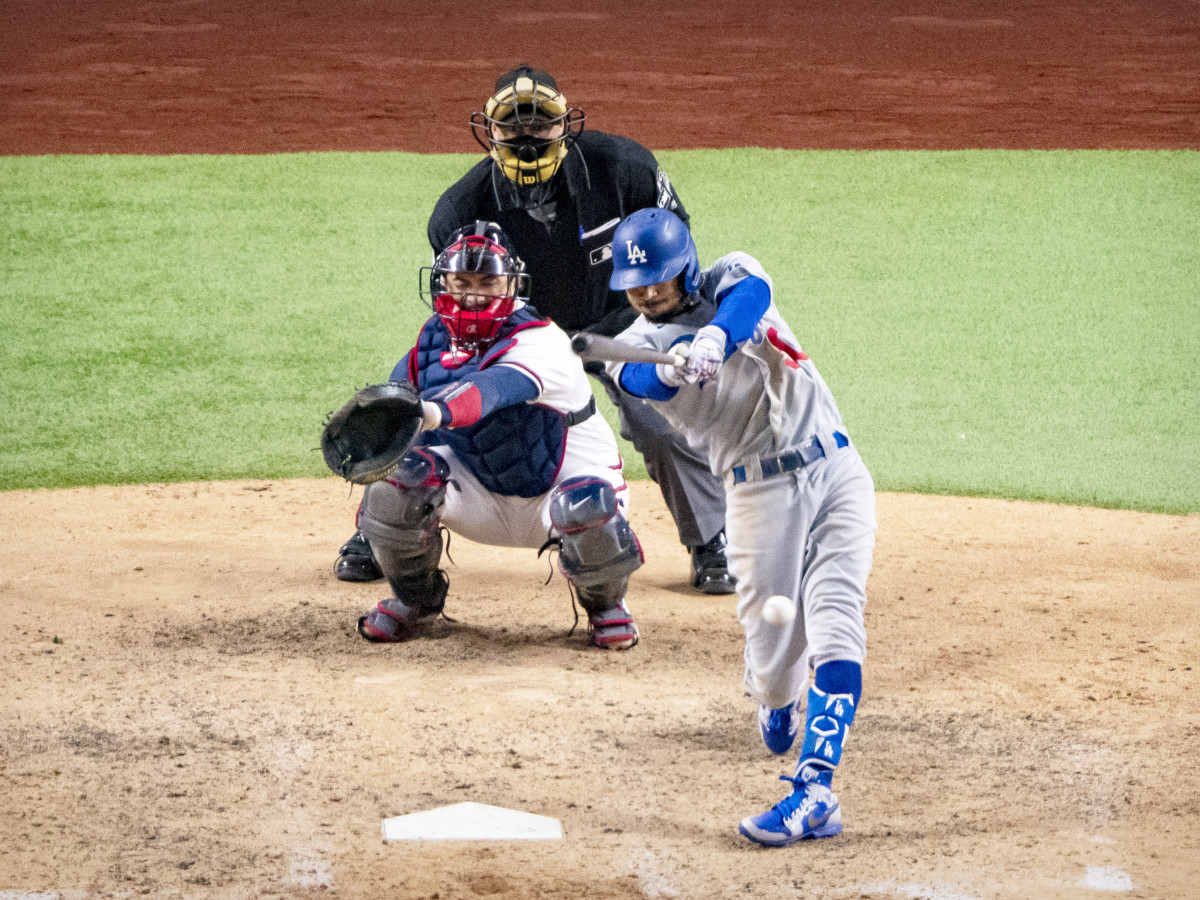 Oct 16, 2020; Arlington, Texas, USA; Los Angeles Dodgers right fielder Mookie Betts (50) singles and drives in a run against the Atlanta Braves during the seventh inning in game five of the 2020 NLCS at Globe Life Field.