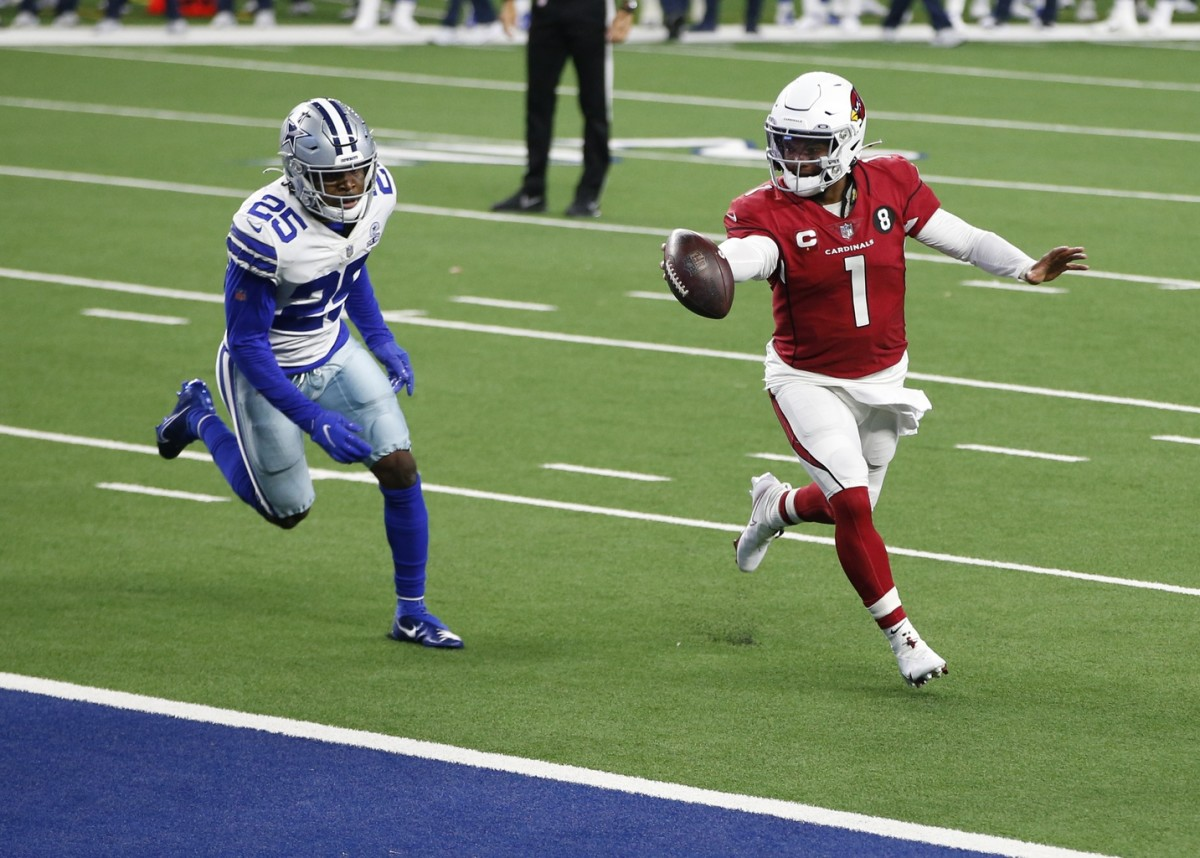 Arizona Cardinals quarterback Kyler Murray (1) runs for a touchdown against Dallas Cowboys free safety Xavier Woods (25) in the third quarter at AT&T Stadium.