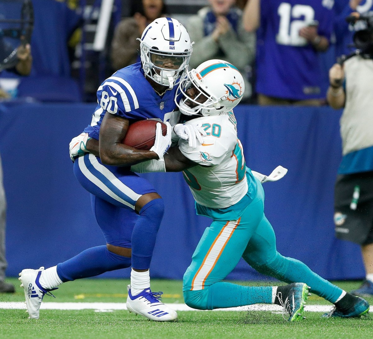 Indianapolis Colts wide receiver Chester Rogers (80) fights for a first down as he is hit by Miami Dolphins free safety Reshad Jones (20) in the fourth quarter of their game at Lucas Oil Stadium on Sunday, Nov. 25, 2018.© Matt Kryger/IndyStar