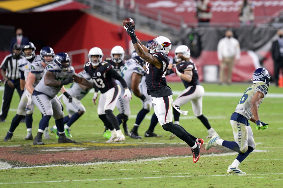Arizona Cardinals linebacker Isaiah Simmons (48) intercepts a pass by Seattle Seahawks quarterback Russell Wilson (left) intended for Seattle Seahawks wide receiver Tyler Lockett (16) during overtime at State Farm Stadium.