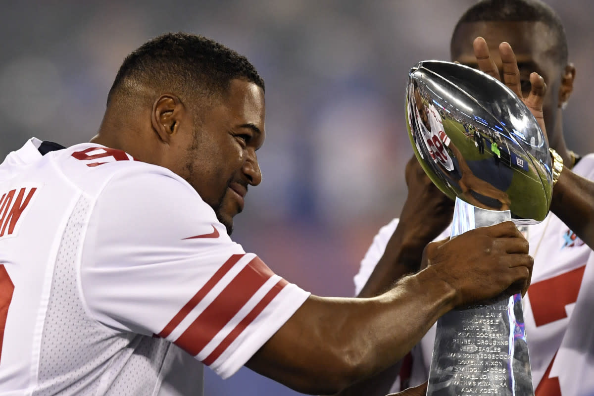 Former Giants player Michael Strahan walks onto the field with the Vince Lombardi Trophy from Super Bowl XLII during the halftime ceremony in the game against the Lions at MetLife Stadium, Sept. 18, 2017.