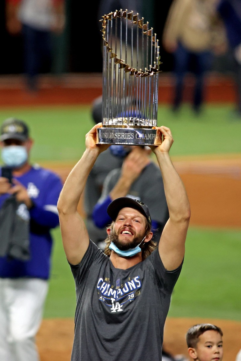 Oct 27, 2020; Arlington, Texas, USA; Los Angeles Dodgers starting pitcher Clayton Kershaw (22) celebrates with the Commissioner's Trophy after the Los Angeles Dodgers beat the Tampa Bay Rays to win the World Series in game six of the 2020 World Series at Globe Life Field. Mandatory Credit: Tim Heitman-USA TODAY Sports