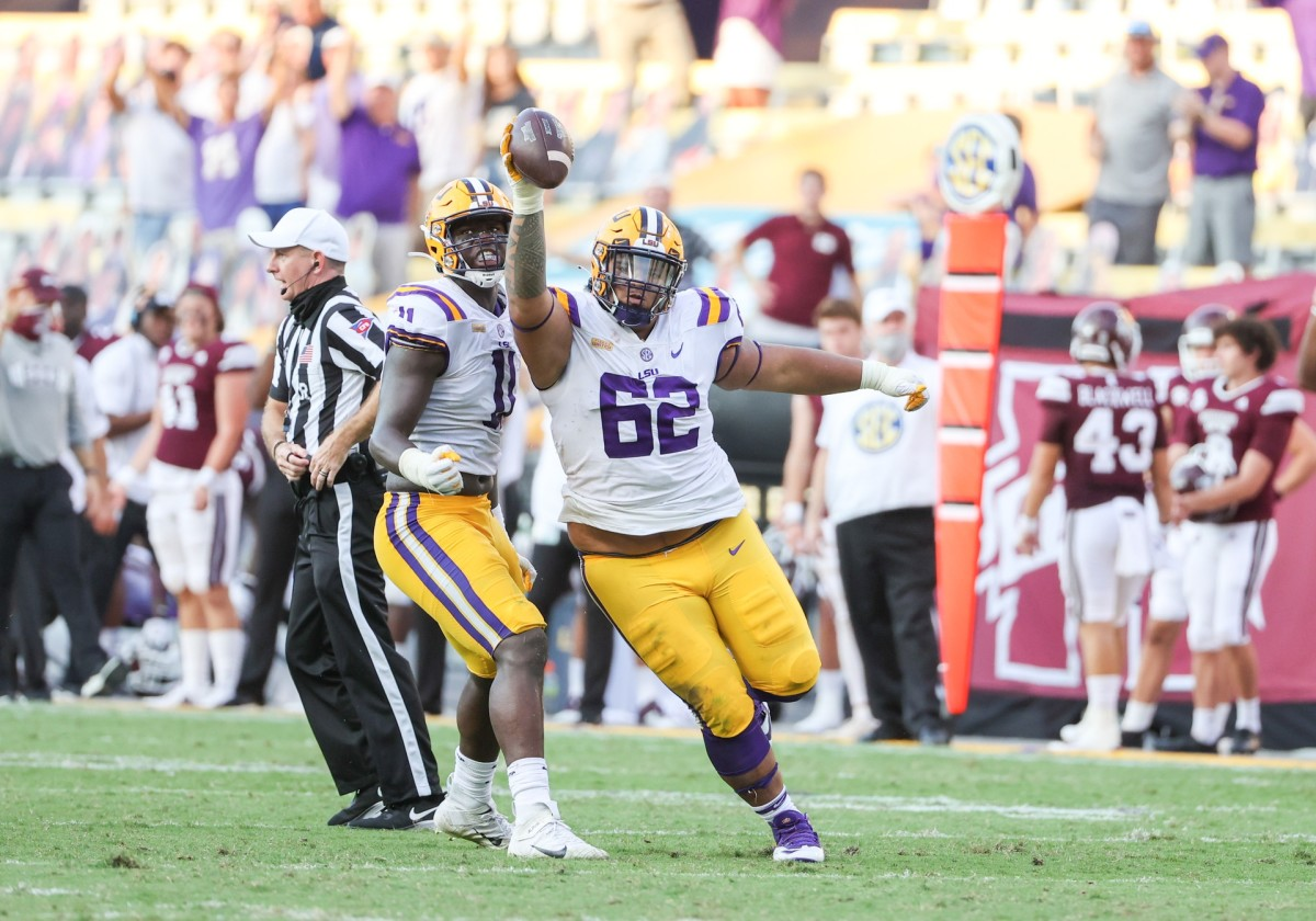 Sep 26, 2020; Baton Rouge, Louisiana, USA; LSU Tigers nose tackle Siaki Ika (62) reacts with defensive lineman Ali Gaye (11) against the Mississippi State Bulldogs during the second half at Tiger Stadium.