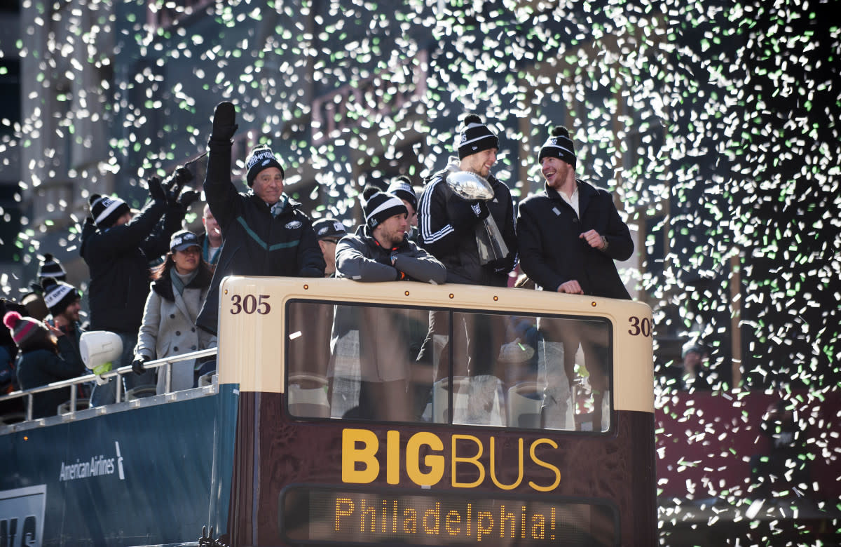 Confetti falls as (from right) QB Carson Wentz, backup QB Nate Sudfeld, Super Bowl MVP Nick Foles and owner Jeffrey Lurie ride a float during the Eagles Super Bowl LII victory parade, Feb. 8, 2018.