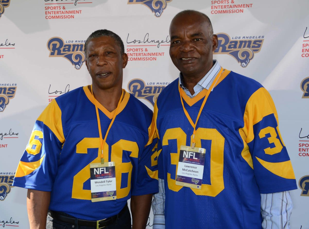 Former Rams running backs Wendell Tyler (26) and Lawrence McCutcheon (30) pose at an NFL All-Access event at the Los Angeles Memorial Coliseum in 2016.