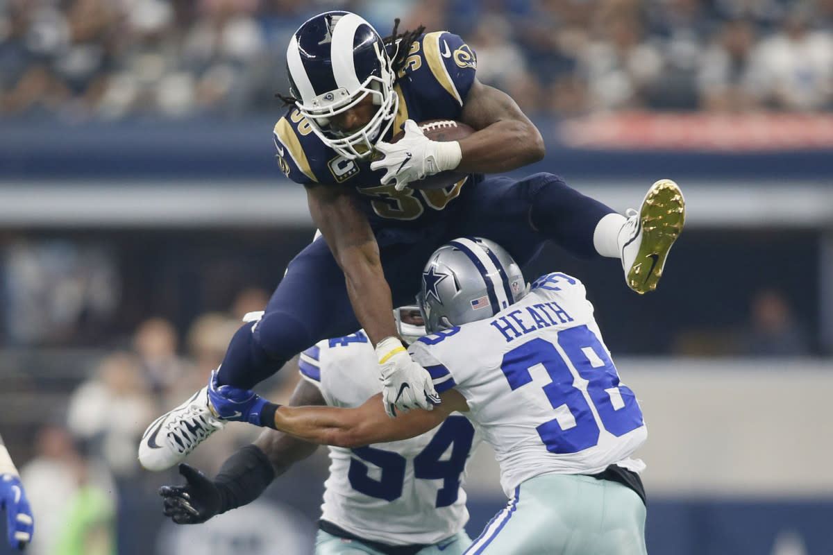 Rams running back Todd Gurley hurdles over Cowboys safety Jeff Heath during a 2017 game. Gurley is among the greatest running backs in Rams history.