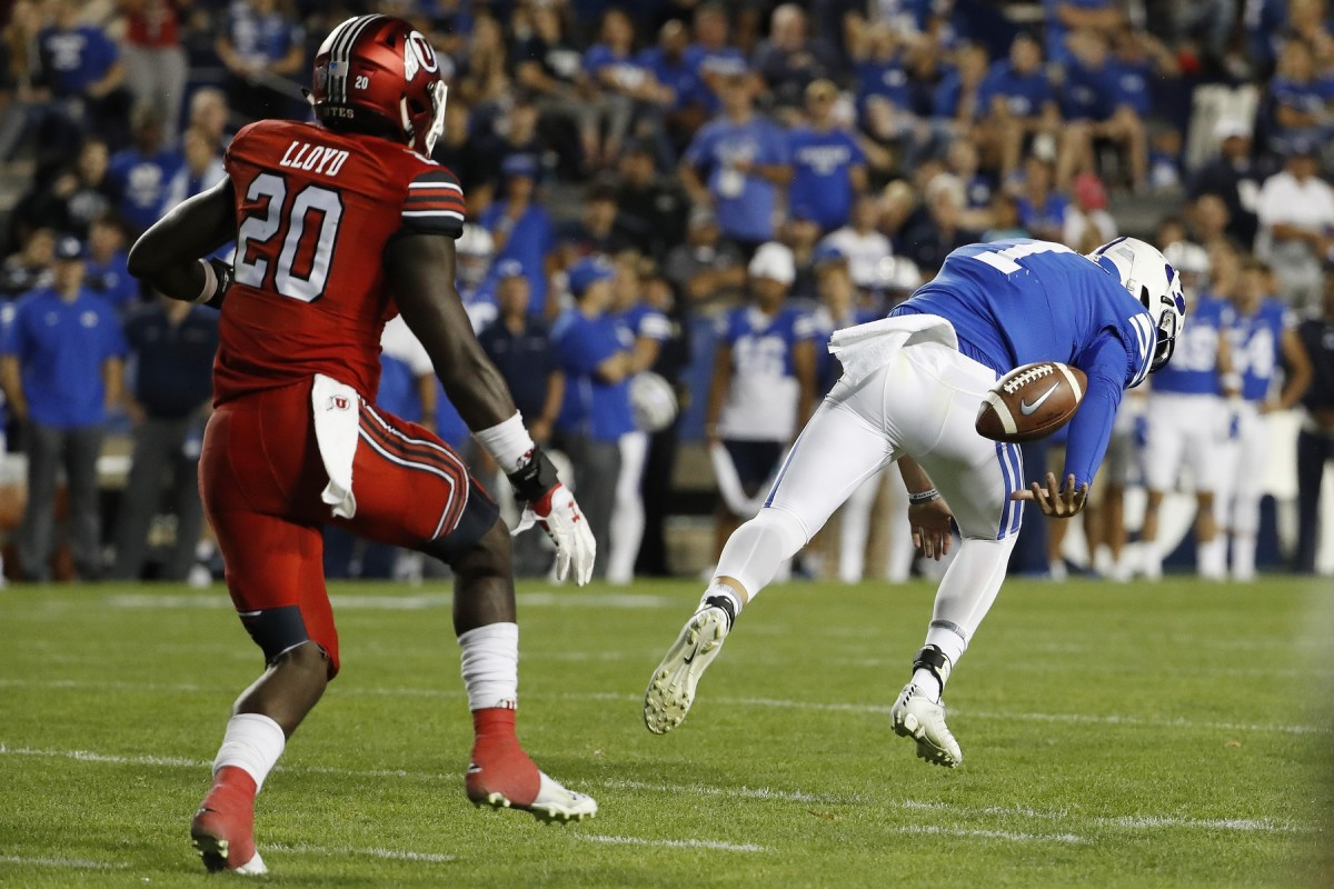 Aug 29, 2019; Provo, UT, USA; Brigham Young Cougars quarterback Zach Wilson (1) fumbles the snap on a two-point conversion attempt against Utah Utes linebacker Devin Lloyd (20) in the fourth quarter at LaVell Edwards Stadium.