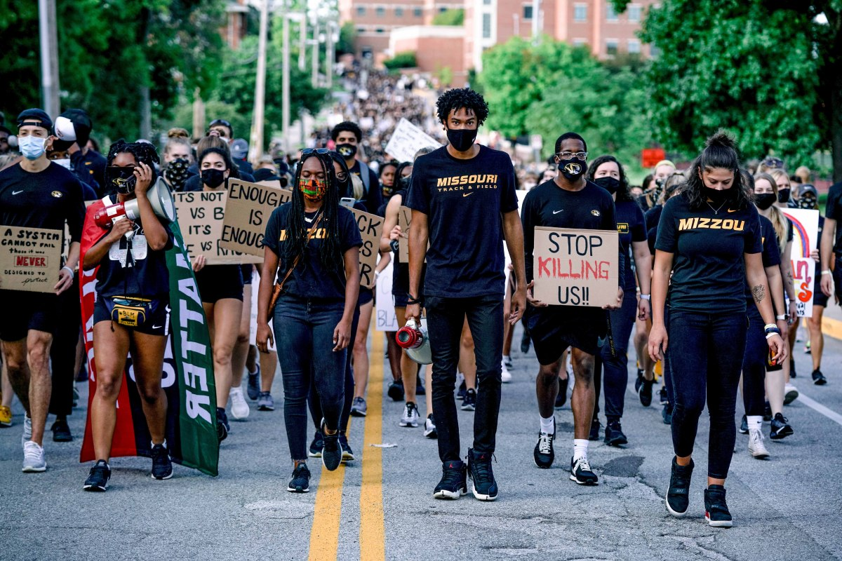 In September, sprinter Suggs (center) led a march of Tigers athletes and their supporters.
