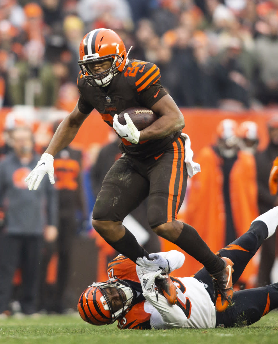 Browns running back Nick Chubb (24) breaks a tackle from Bengals cornerback Darius Phillips (23) during the third quarter at FirstEnergy Stadium in Cleveland, Dec. 23, 2018.