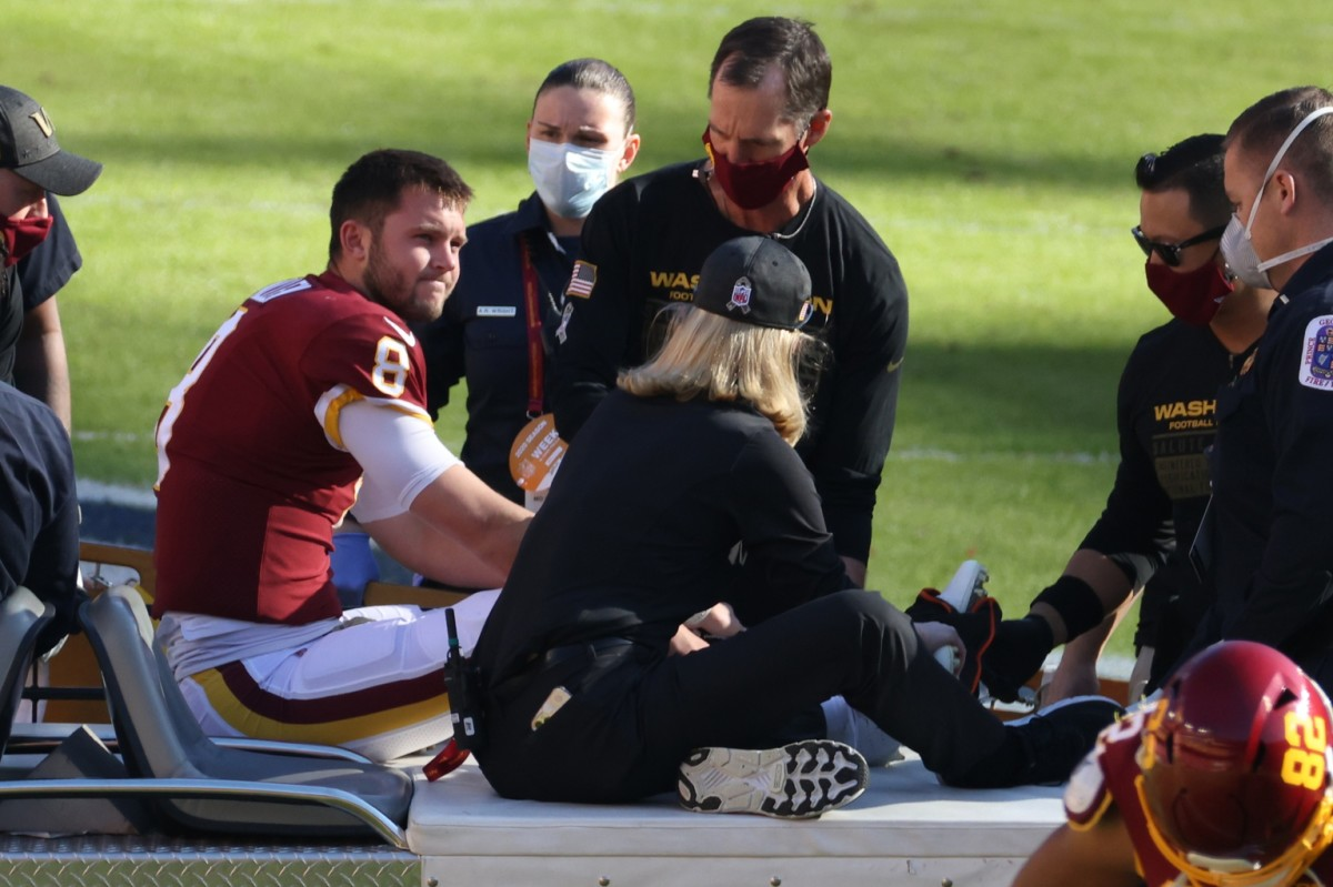 Nov 8, 2020; Landover, Maryland, USA; Washington Football Team quarterback Kyle Allen (8) sits on a cart after being injured by being tripped by New York Giants strong safety Jabrill Peppers (not pictured) while scrambling in the first quarter at FedExField.