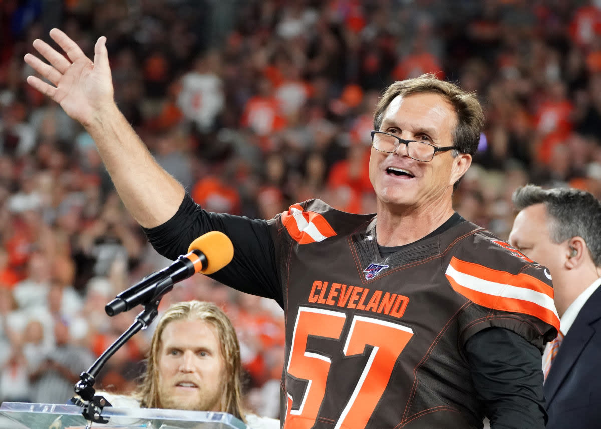 Former Browns linebacker Clay Matthews Jr. (57) speaks as he is inducted into the Browns Ring of Honor at halftime of a 2019 game against the Rams. His son and Rams linebacker Clay Matthews III can be seen in the background.