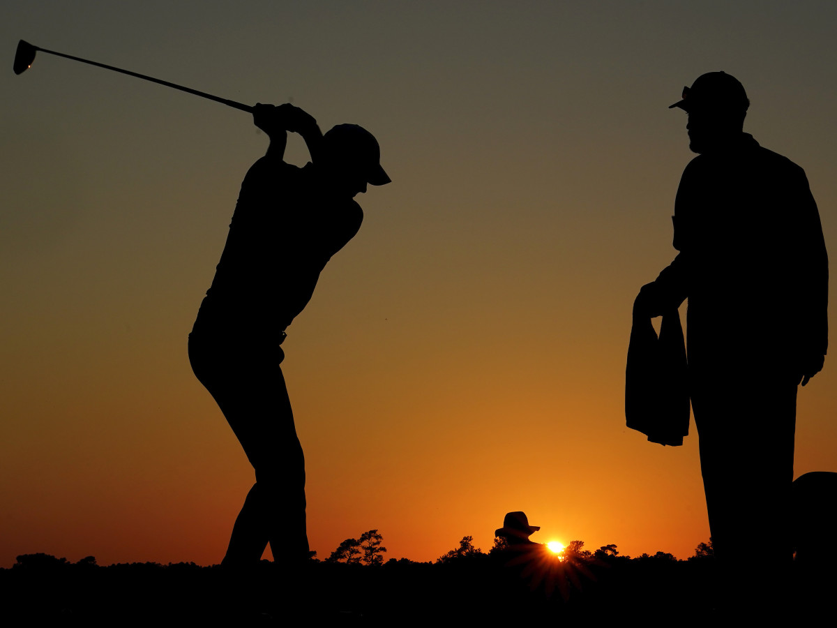 Jordan Spieth prepares for his tee shot off the tenth tee as the sun sets during the second round