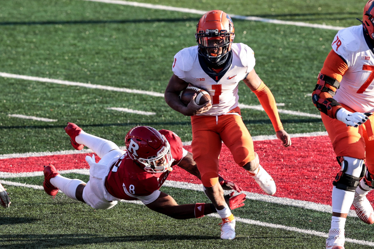 Illinois Fighting Illini quarterback Isaiah Williams (1) carries the ball as Rutgers Scarlet Knights linebacker Tyshon Fogg (8) dives for the tackle during the second half at SHI Stadium.
